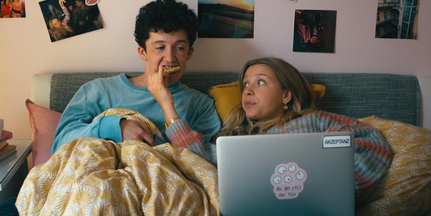il protagonista e la compagna sono a letto: lui sta mangiando una brioche, lei è al computer ed evidentemente ce l'ha col ragazzo - nerdface