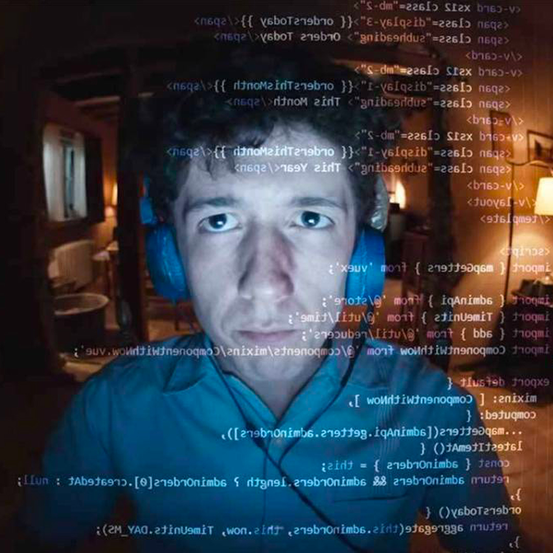 il protagonista è in primo piano, indossa delle cuffie azzurre e in trasparenza si vedono i codici che sta programmando al computer, come se la prospettiva fosse da dentro lo schermo - nerdface