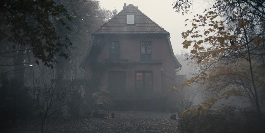 una casa immersa nella foschia, in mezzo a un bosco - nerdface