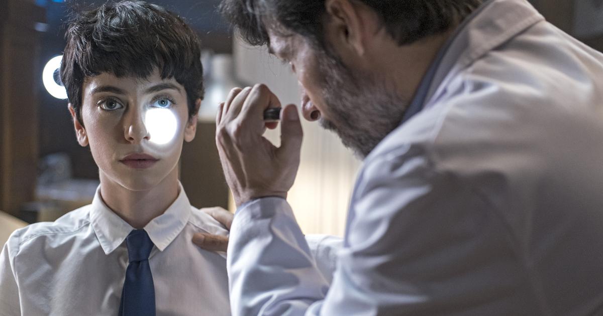 un medico punta una piccola torcia verso l'occhio di una giovane paziente - nerdface