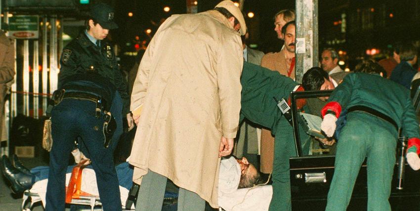 il corpo di una vittima della mafia e deposto su una barella, circondato da medici e poliziotti - nerdface