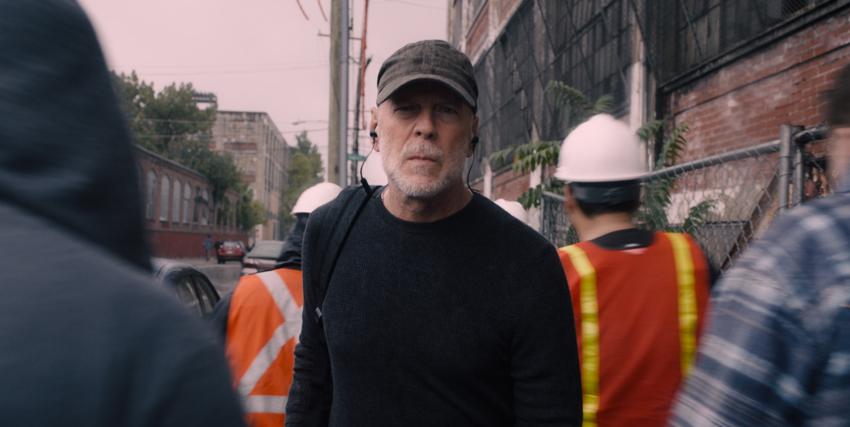 Primo piano di Bruce Willis in mezzo a degli operai nel film Glass - nerdface