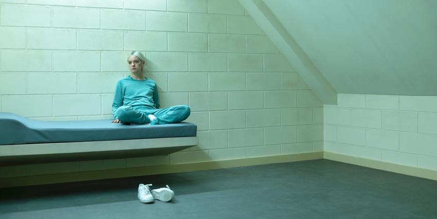 hanna è in tenuta carceraria azzurrina dentro una cella bianca, seduta su una branda - nerdface