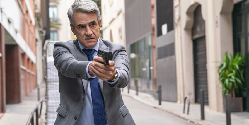 un uomo ben vestito punta una pistola verso qualcuno, in mezzo a una strada - nerdface