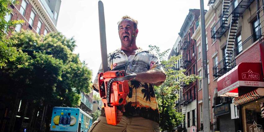 il protagonista bransice una motosega nel mezzo di una strada e urla felice - nerdface
