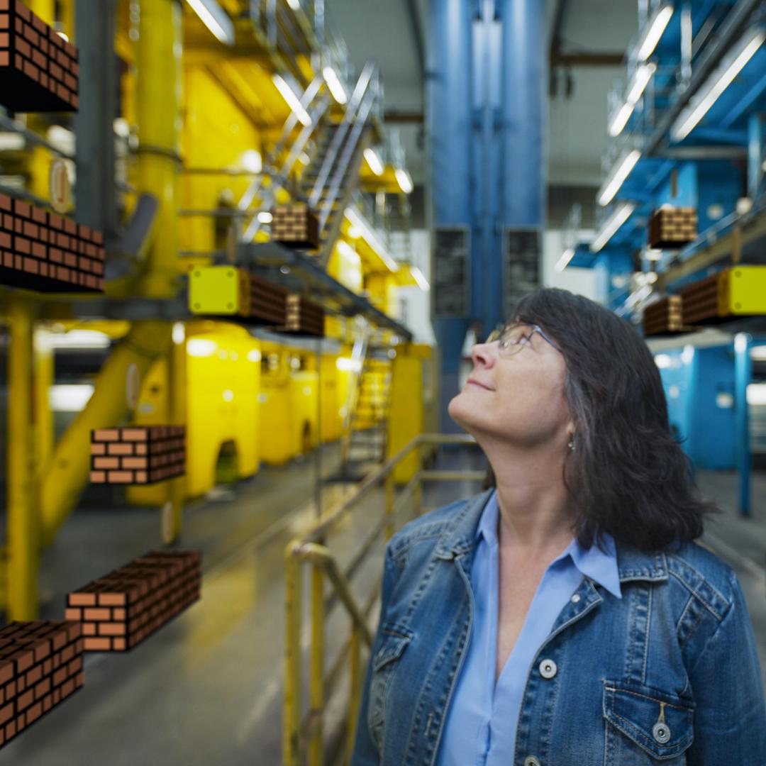 una donna sta osservando una serie di alti scaffali gialli sui quali sono inseriti i tipici mattoncini di super mario - nerdface