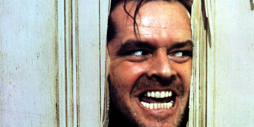 Primo piano di Jack Nicholson attraverso la porta spaccata con la sua accetta in Shining - nerdface