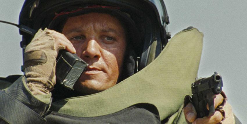 Primo piano di Jeremy Renner in The Hurt Locker con pistola e trasmittente nelle mani - nerdface