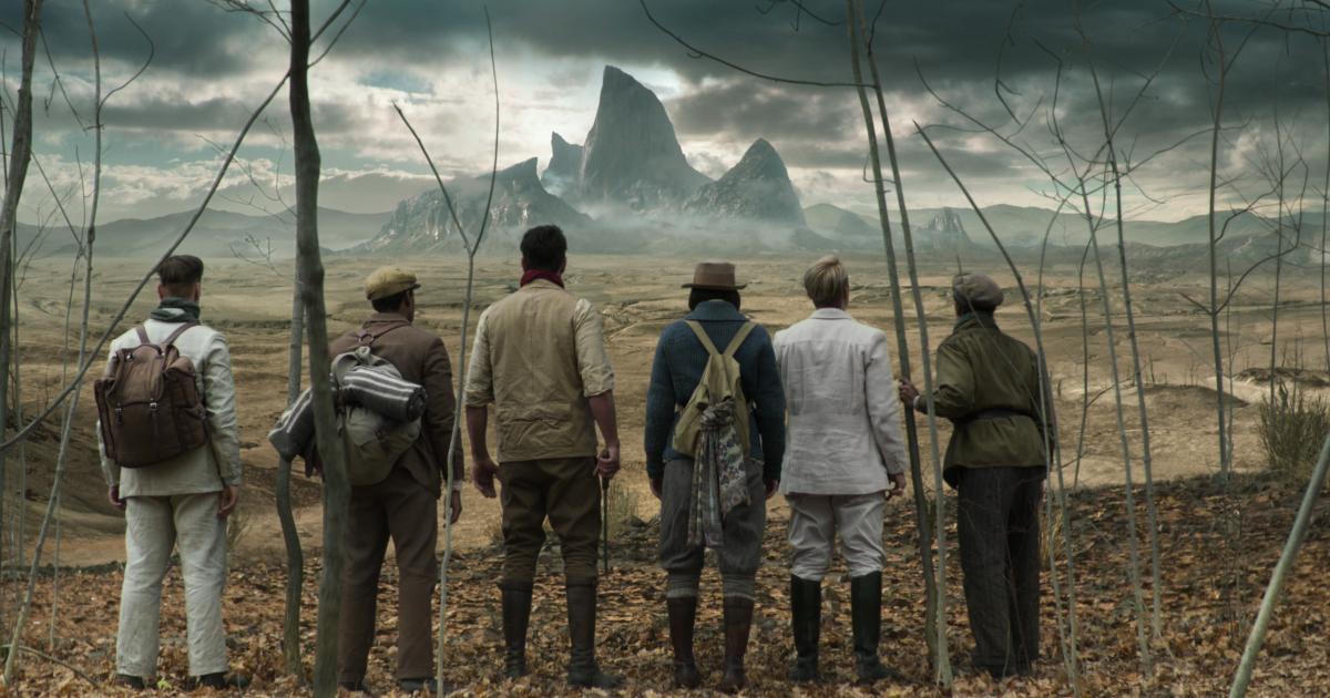 un gruppo di esploratori osserva le vette di una montagna in lontananza - nerdface
