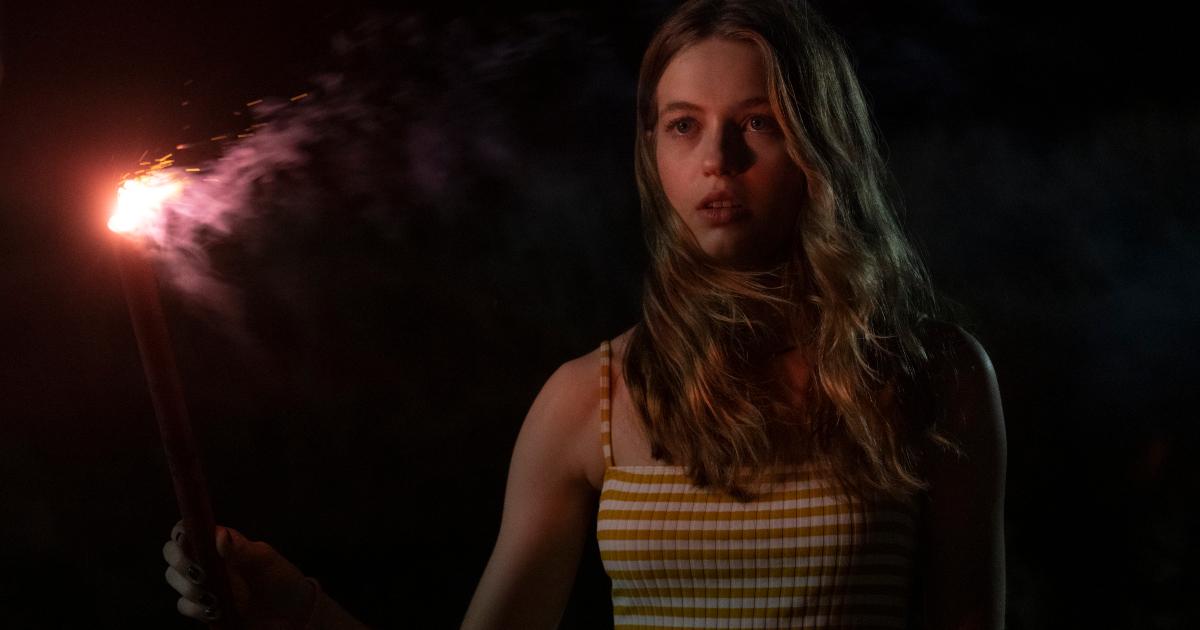 la protagonista di panic tiene in mano una torcia rossa, in piena notte - nerdface
