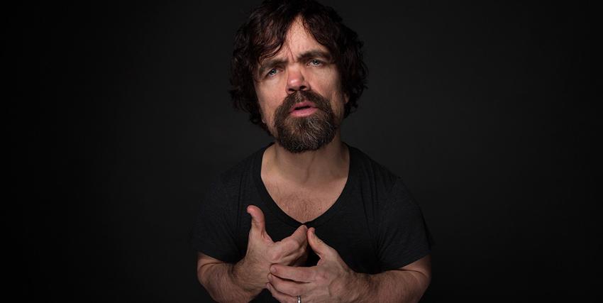 peter dinklage si tiene le mani al petto in un ritratto fotografico - nerdface