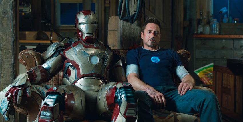 Robert Downey Jr. seduto accanto all'armatura di Iron Man - nerdface