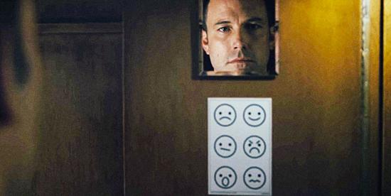 ben affleck come sempre inespressivo è di fronte a uno specchio sul quale sono un disegno attaccato raffigura diverse espressioni del volto, ma tanto non servirà - nerdface