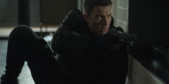 completamente vestito di nero, ben affleck è accovacciato addosso a un muro e imbraccia un fucile - nerdface