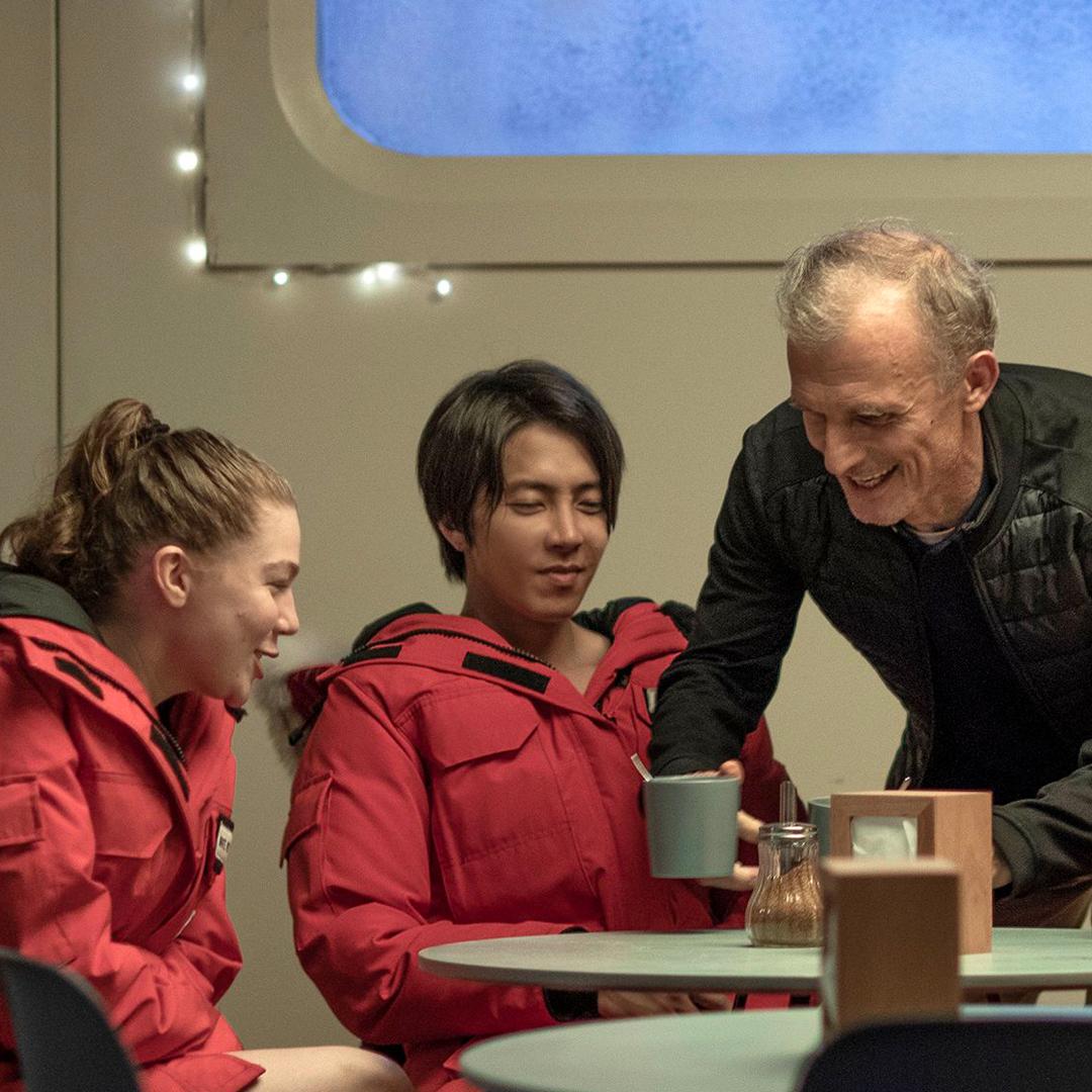 due scienziati in tuta termica sono seduti nella base antartica e un terzo uomo serve loro una bevanda calda - nerdface
