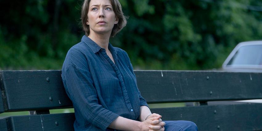 una donna è seduta su una panchina con le mani e conserte e guarda distrattamente alla sua destra - nerdface