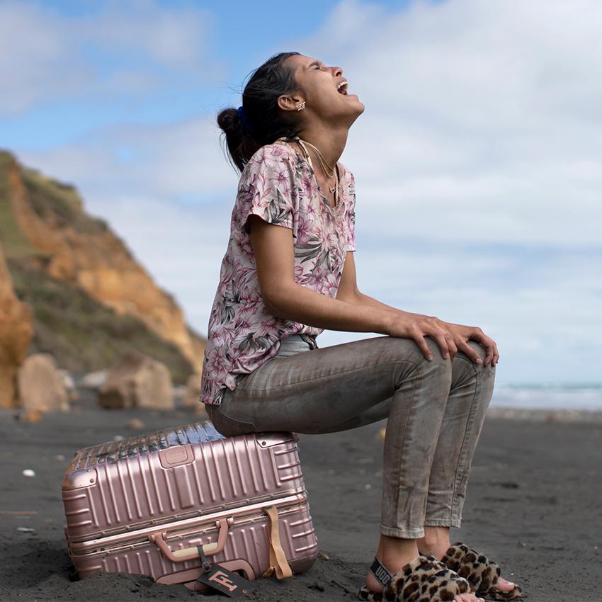 una ragazza è seduta sulla sua valigia rosa, su una spiaggia, e urla il so dolore - nerdface