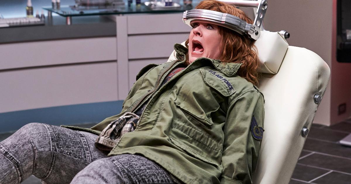 Una delle due protagoniste di Thunder Force su una poltrona con un apparecchio attorno alla testa - nerdface