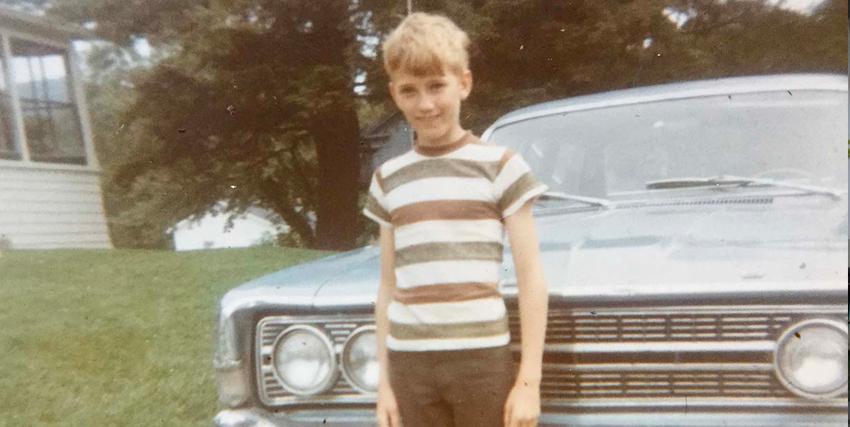 una foto d'epoca mostra un bambino sorridente davanti una tipica auto americana - nerdface