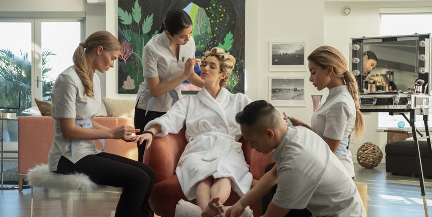 una donna seduta e in accappatoio si sta affidando alle cure estetiche di numerose persone - nerdface