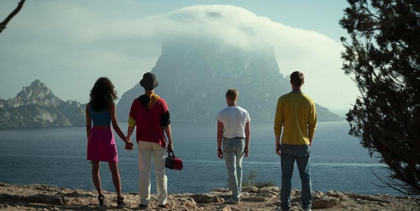 quattro ragazzi ripresi di spalle osservano il panorama do un'isola in mezzo al mare avvolta da una. nuvola - nerdface